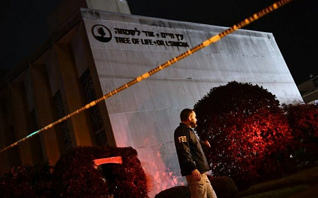 An FBI agent stands behind a police cordon outside the Tree of Life Synagogue after a shooting there left 11 people dead in the Squirrel Hill neighborhood of Pittsburgh on October 27, 2018. (Brendan Smialowski / AFP)