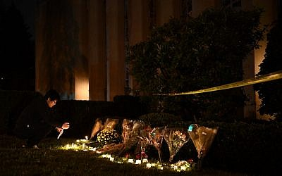 A man kneels to light a candle beneath a police cordon outside the Tree of Life Synagogue in Pittsburgh, after a shooting there left 11 people dead on October 27, 2018 (Brendan Smialowski / AFP)