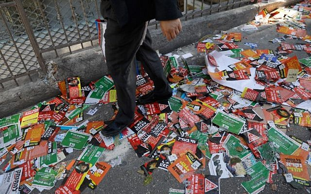 A Jewish man walks in a street littered with election campaign posters for the upcoming Jerusalem municipal elections, in Jerusalem on October 28, 2018. (MENAHEM KAHANA / AFP)