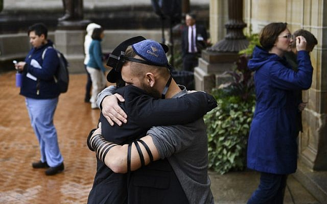 People hug as they arrive for a vigil, for the shoting at the Tree of Life synagogue the day before, at the Allegheny County Soldiers Memorial on October 28, 2018, in Pittsburgh, Pennsylvania.  (Brendan Smialowski / AFP)