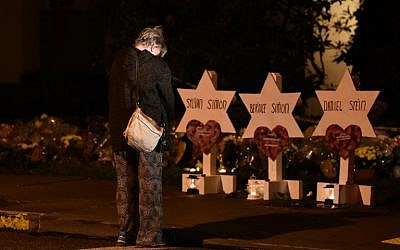 A woman bows her head in front of a memorial on October 28, 2018, at the Tree of Life synagogue after a shooting there left 11 people dead in the Squirrel Hill neighborhood of Pittsburgh on October 27.  2018 (Photo by Brendan SMIALOWSKI / AFP)