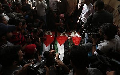 Mourners carry the bodies of three teens, wrapped in Palestinian flags, who were killed in an Israeli airstrike during their funeral in the town of Deir el-Balah, central Gaza Strip, October 29, 2018. (MAHMUD HAMS / AFP)