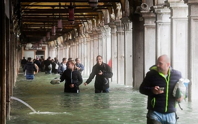 Tourists under arches next to the flooded St Mark's Square during a high-water alert in Venice on October 29, 2018 (Photo by Miguel MEDINA / AFP)