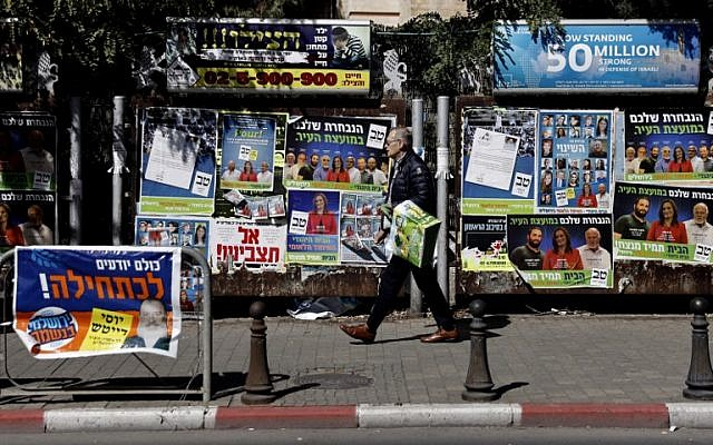 An Israeli man hangs campaign posters for local elections in the center of Jerusalem on October 30, 2018. (Thomas Coex/AFP)