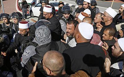 Israeli security forces stand guard as Druze men protest against municipal elections in front of a polling center in the village of Majdal Shams in the Golan Heights on October 30, 2018. (Photo by JALAA MAREY / AFP)