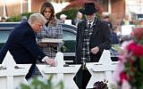 US President Donald Trump and First Lady Melania Trump, accompanied by Rabbi Jeffrey Myers, place stones and flowers on a memorial as they pay their respects at the Tree of Life synagogue in Pittsburgh, Pennsylvania, on October 30, 2018. (Saul Loeb/AFP)