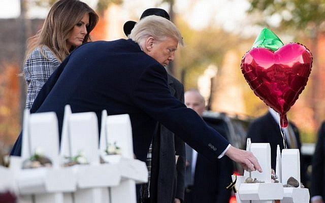 US President Donald Trump and First Lady Melania Trump, alongside Rabbi Jeffrey Myers, place stones and flowers on a memorial as they pay their respects at the Tree of Life Synagogue following last weekend's shooting in Pittsburgh, Pennsylvania, October 30, 2018. (Photo by SAUL LOEB / AFP)