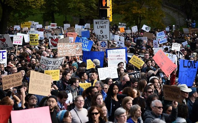 """People gather to protest the arrival of US President Donald Trump as he visits the Tree of Life Congregation on October 30, 2018 in Pittsburgh, Pennsylvania. - Scores of protesters took to the streets of Pittsburgh to denounce a visit by US President Donald Trump in the wake of a mass shooting at a synagogue that left 11 people dead. Demonstrators gathered near the Tree of Life synagogue, where the shooting took place, holding signs that read """"President Hate, Leave Our State!"""" and """"Trump, Renounce White Nationalism Now."""" (Photo by Brendan SMIALOWSKI / AFP)"""