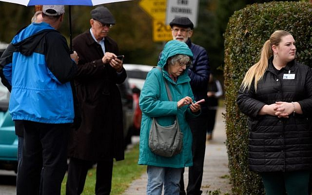 Residents check their phones near the site of a mass shooting at the Tree of Life Synagogue in the Squirrel Hill neighborhood on October 27, 2018 in Pittsburgh, Pennsylvania. (Jeff Swensen/Getty Images/AFP)
