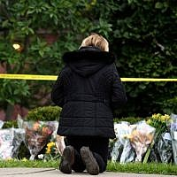 A mourner prays after laying flowers at the site of the mass shooting that killed 11 people and wounded 6 at the Tree Of Life Synagogue on October 28, 2018 in Pittsburgh, Pennsylvania.  (Jeff Swensen/Getty Images/AFP)