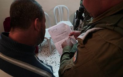 An IDF soldier notifying a relative of terror suspect Ashraf Na'alowa of the military's intention to demolish his home, October 15, 2018. (IDF Spokesperson's Unit)