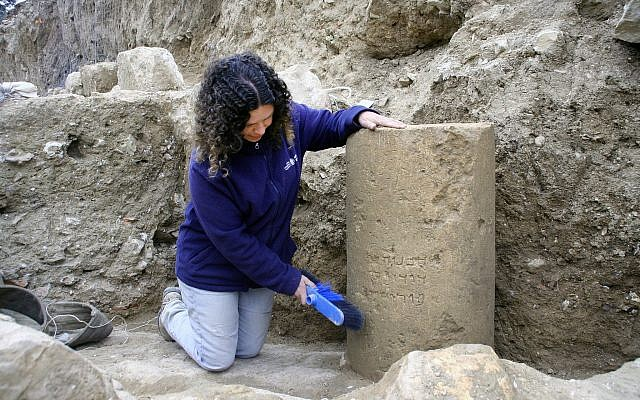 Danit Levi, director of the excavations on behalf of the Israel Antiquities Authority, beside the inscription as found in the field near the Jerusalem International Convention Center, winter 2018. (Yoli Shwartz, IAA)