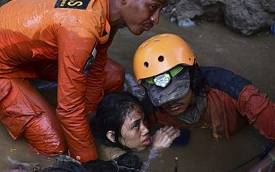 Rescuers evacuate an earthquake survivor by a damaged house following earthquakes and tsunami in Palu, Central Sulawesi, Indonesia, on September 30, 2018. (AP Photo/Arimacs Wilander)