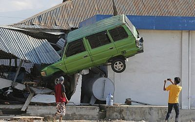 A man takes a photo of a car lifted into the air with his mobile phone following a massive earthquake and tsunami at Talise beach in Palu, Central Sulawesi, Indonesia, Oct. 1, 2018 (AP Photo/Tatan Syuflana)