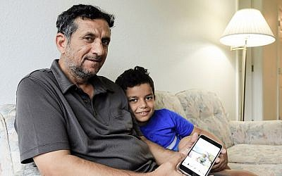 In this September 29, 2018 photo, Hadi Mohammed sits with his 9 year old son Mohammed Ghaleb, as he displays a photo of his son as a baby in Baghdad, in their Lincoln, Nebraska apartment. (AP Photo/Nati Harnik)