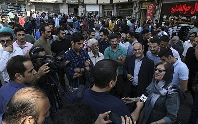 A woman seeking to buy US dollars, bottom right, speaks with The Associated Press in downtown Tehran, Iran, October 2, 2018. (AP Photo/Vahid Salemi)