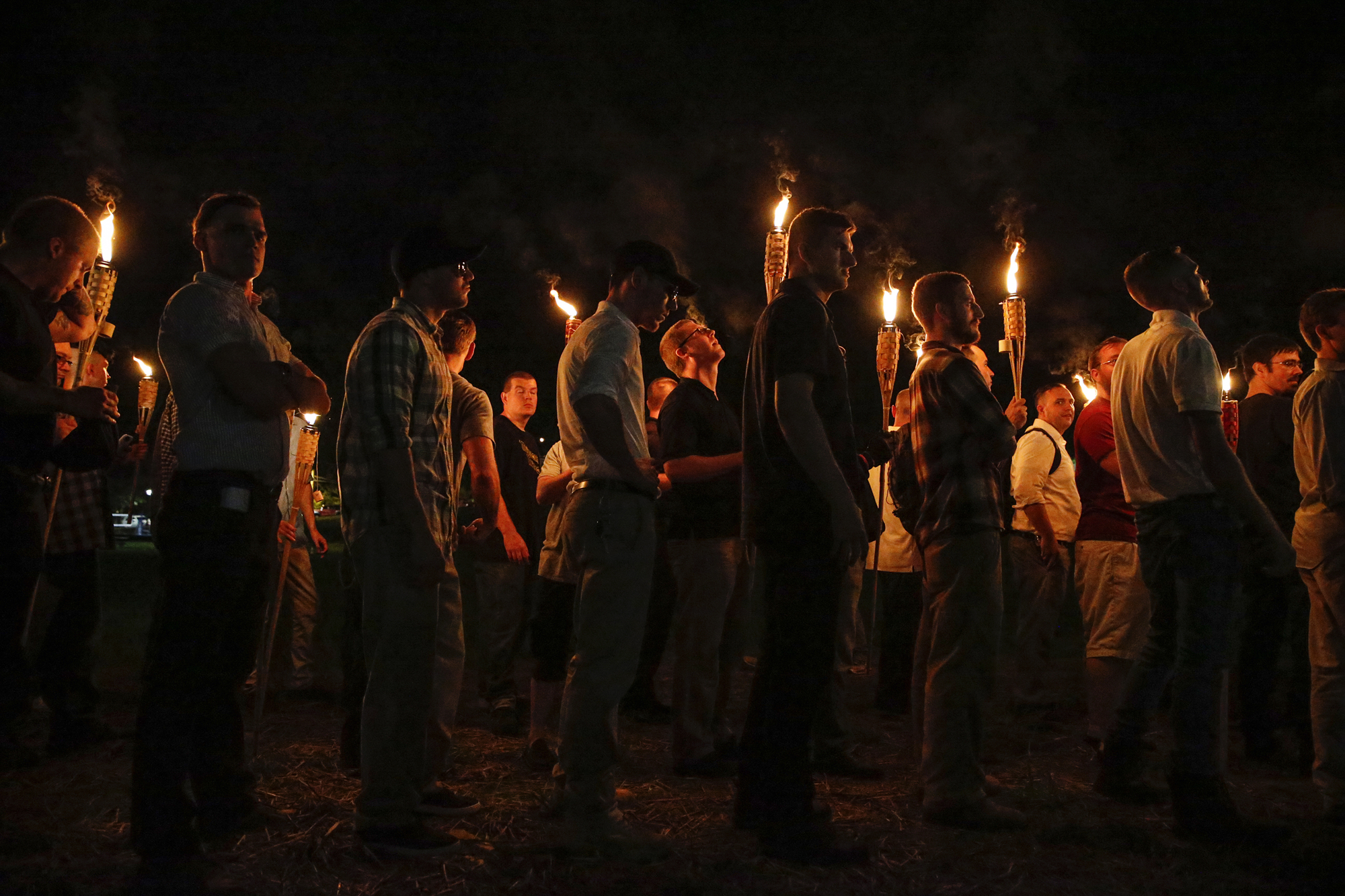 In this August 11, 2017, photo, multiple white nationalist groups march with torches through the University of Virginia campus in Charlottesville, Virginia. (Mykal McEldowney/The Indianapolis Star via AP)