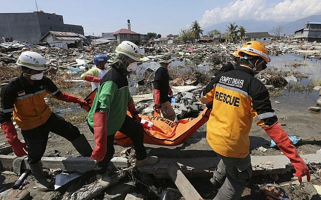 An Indonesian rescue team carries the body of a victim following an earthquake and tsunami in Palu, Central Sulawesi, Indonesia, October 3, 2018. (Tatan Syuflana/AP)