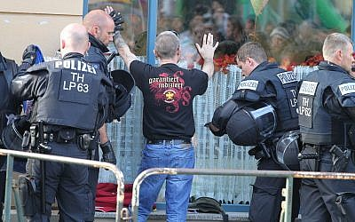 In this photo from October 6, 2018, police officers search a visitor of a far neo-Nazi rock concert in Aploda, Germany. Slogan on the shirt reads 'guaranteed indexed.' (Sebastian Haak/dpa via AP)
