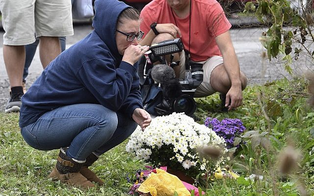 People place flowers, Sunday, Oct. 7, 2018, at the scene where 20 people died as the result of a limousine crashing into a parked and unoccupied SUV at an intersection a day earlier, in Schoharie, N.Y. (AP Photo/Hans Pennink)