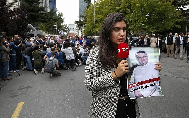A journalist holding a poster of missing Saudi writer Jamal Khashoggi, speaks to camera near the Saudi Arabia consulate in Istanbul, October 8, 2018. (AP Photo/Lefteris Pitarakis)