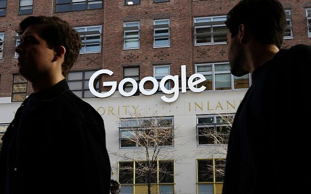 People walk by Google's offices in New York, December 4, 2017. (AP Photo/Mark Lennihan, File)