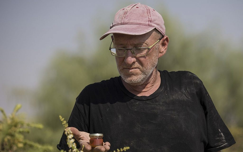 In this September 17, 2018 photo, Guy Erlich holds a jar of frankincense honey at his farm near Almog, an Israeli settlement and kibbutz in the Jordan Valley, in the West Bank. (AP Photo/Tsafrir Abayov)