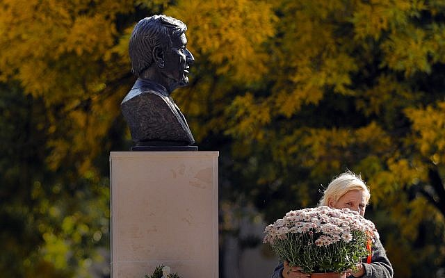 A municipal worker carries flowers next to the bust of Holocaust survivor and Nobel laureate Elie Wiesel in Bucharest, Romania,  October 9, 2018. (Vadim Ghirda/AP)