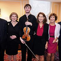 """In this photo provided by Chris Lee, Juilliard student Nathan Meltzer, center, poses with the """"Ames, Totenberg"""" Stradivari of 1734 violin loaned to him by the daughters of the late violinist Roman Totenberg, October 9, 2018 in New York. (Chris Lee via AP)"""