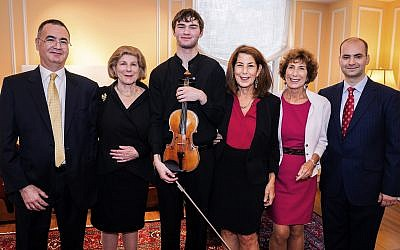 "In this photo provided by Chris Lee, Juilliard student Nathan Meltzer, center, poses with the ""Ames, Totenberg"" Stradivari of 1734 violin loaned to him by the daughters of the late violinist Roman Totenberg, October 9, 2018 in New York. (Chris Lee via AP)"