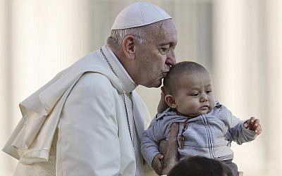 Pope Francis kisses a child as he arrives with the popemobile in St.Peter's Square to held his weekly general audience at the Vatican, Wednesday, Oct. 10, 2018. (AP Photo/Gregorio Borgia)