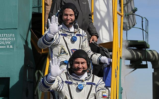 US astronaut Nick Hague, right, and Russian cosmonaut Alexey Ovchinin, crew members of the mission to the International Space Station wave as they board the rocket prior to the launch of Soyuz-FG rocket at the Russian leased Baikonur cosmodrome, Kazakhstan, October 11, 2018. (Yuri Kochetkov, Pool Photo via AP)