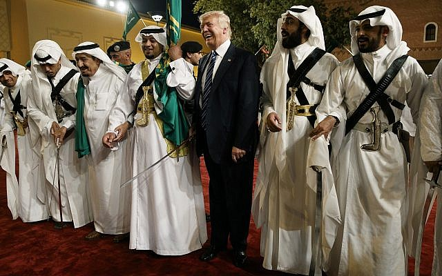 In this photo from May 20, 2017, US President Donald Trump holds a sword and dances with traditional dancers during a welcome ceremony at Murabba Palace, in Riyadh, Saudi Arabia. (AP Photo/Evan Vucci, File)