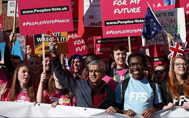 London Mayor Sadiq Khan, front center, holds a klaxon horn, as he joins protesters in the People's Vote March for the Future, in London, on October 20, 2018. (Yui Mok/PA via AP)