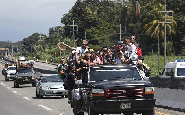 Central American migrants making their way to the US in a large caravan fill the truck of a driver who offered them the free ride, as they arrive to Tapachula, Mexico, on October 21, 2018. (AP Photo/Moises Castillo)