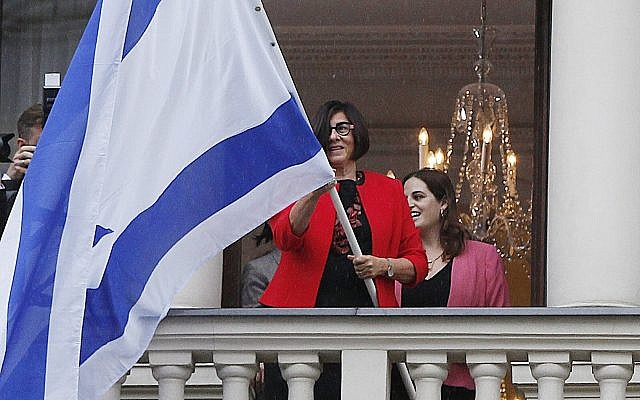 Israeli Ambassador Anna Azari holds the Israeli flag from a balcony of the historic Bristol Hotel in Warsaw, Poland, during a ceremony on Tuesday, Oct. 23, 2018. The flag hanging was a re-enactment ceremony marking the 70th anniversary of Israel's first diplomatic outpost as a new nation at the same spot. (AP Photo/Czarek Sokolowski)