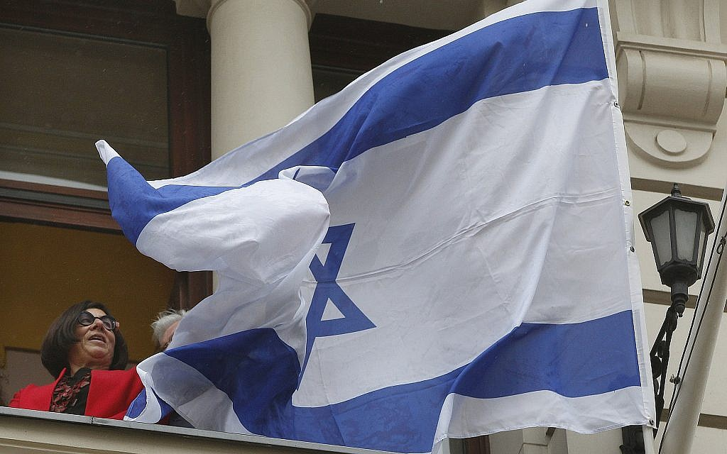 Israeli Ambassador Anna Azari holds the Israeli flag from a balcony of the historic Bristol Hotel in Warsaw, Poland, during a ceremony on Tuesday, Oct. 23, 2018.  (AP/Czarek Sokolowski)
