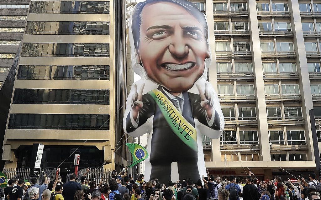 In this Sept. 9, 2018 file photo, supporters of presidential frontrunner Jair Bolsonaro, exhibit a large, inflatable doll in his image as they march along Paulista Avenue to show support for him in Sao Paulo, Brazil.  (AP Photo/Andre Penner)