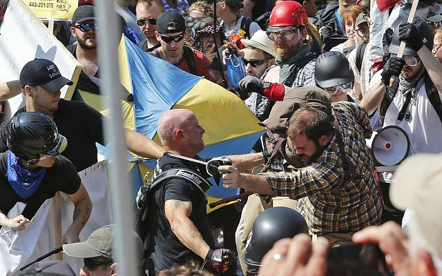 Illustrative: In this photo from August 12, 2017, white supremacist demonstrators clash with counter demonstrators at the entrance to Lee Park in Charlottesville, Virginia. (AP Photo/Steve Helber, File)