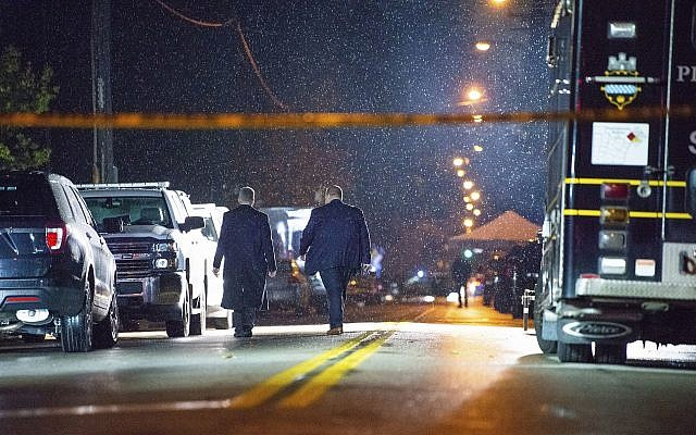 The FBI investigates in the rain after a deadly shooting at the Tree of Life Congregation, a Conservative synagogue, on Saturday, October 27, 2018, in the Squirrel Hill section of Pittsburgh, Pennsylvania. (Andrew Stein/Pittsburgh Post-Gazette via AP)