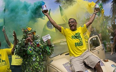Supporters of presidential front-runner Jair Bolsonaro sing the national anthem outside his residence in Rio de Janeiro, Brazil, Sunday, Oct. 28, 2018, during the country's presidential runoff election.(AP Photo/Silvia Izquierdo)