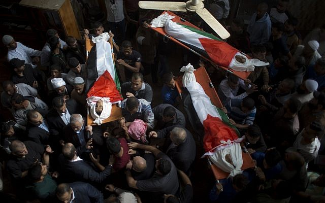 Mourners carry the bodies of three teens, wrapped in Palestinian flags, who were killed in an Israeli airstrike  during their funeral in the town of Deir el-Balah, central Gaza Strip, October 29, 2018. (Khalil Hamra/AP)