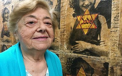 In this October 29, 2018 photo, Auschwitz-Birkenau survivor Magda Brown, 91, stands beside an image of Anne Frank at the Holocaust Center of Pittsburgh. (AP Photo/Allen G. Breed)
