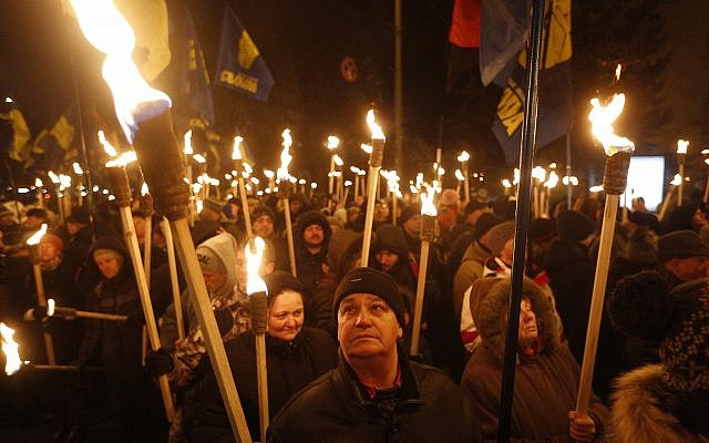 Members of the nationalist Svoboda (Freedom) party carry torches during a rally in Kiev, Ukraine, Jan. 29, 2017, to mark the anniversary of a battle near the town of Kruty (AP Photo/Sergei Chuzavkov)