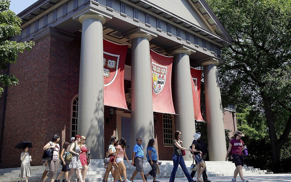 A tour group walks through the campus of Harvard University in Cambridge, Massachusetts. Word of an August 2017 Justice Department inquiry into how race factors into admissions at Harvard University has left top-tier colleges bracing for scrutiny of practices that have boosted diversity levels to new highs. (AP Photo/Elise Amendola, File)