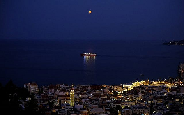 The moon in seen in a partial lunar eclipse over a ship in Zakynthos island on Monday, Aug. 7, 2017. (AP/Petros Karadjias)