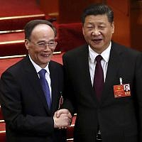 Chinese President Xi Jinping, right, shakes hands with Wang Qishan after Wang was elected vice-president during a plenary session of China's National People's Congress (NPC) in Beijing, March 17, 2018. (AP Photo/Mark Schiefelbein)