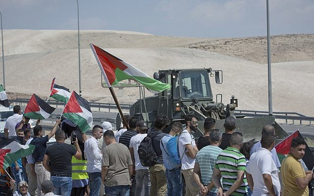 An Israeli army bulldozer passes by protesters flying Palestinian flags and chant anti Israel slogans while they try to block the traffic on the highway passing near the West Bank Bedouin community of Khan al-Ahmar on September 14, 2018. (AP Photo/Nasser Nasser)