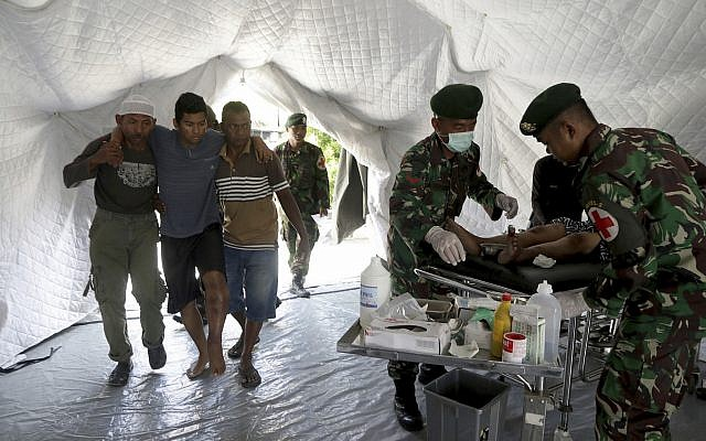 Indonesian soldiers assist earthquake victims to receive medical treatment at a field hospital in Palu, Central Sulawesi, Indonesia, October 2, 2018. (Chandra/AP)