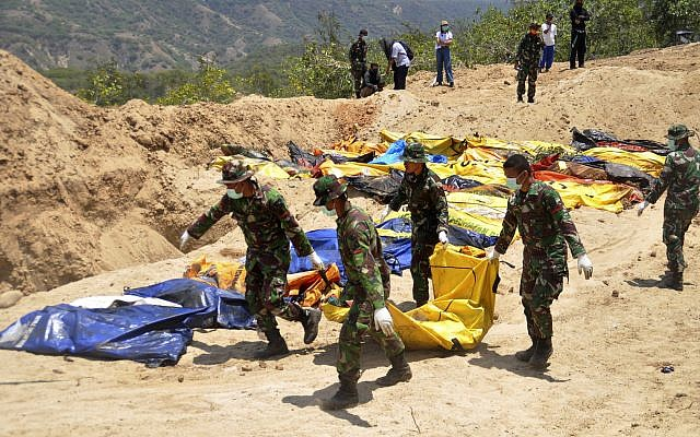 Indonesian soldiers line up the bodies of tsunami and earthquake victims for a mass burial in Palu, Central Sulawesi, Indonesia,October 2. 2018. (Rifki/AP)